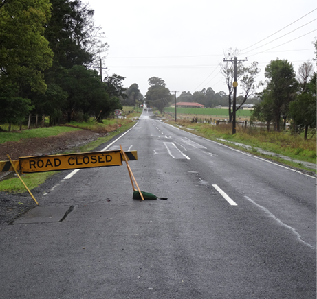 A straight, flat country road runs between fields towards some distant houses. The landscape is wet. A 'road closed' sign is standing across the left lane of the road.