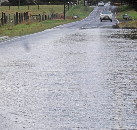 A country road is partially covered with water of unmarked depth. Some cars are approaching the edge of the water. One car is visible in the distance driving away from the flooded area.