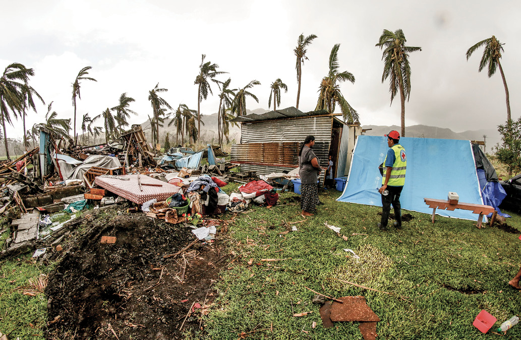 Two people are looking at the damage from the cyclone. A small home is severely damaged, and belongings are strewn about the front yard. The land itself it also damaged, and many palm trees are broken.