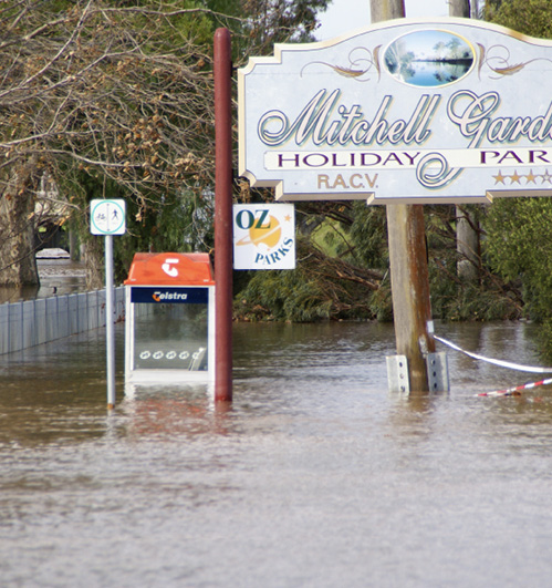 A sign advertising a caravan park is partially underwater. A phone booth is beside the sign, and it is nearly half submerged in the flood waters.