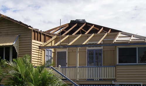 Photo of a home with roof cladding 'flipped off' the roof structure.