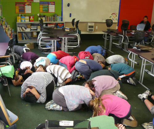 A photo of students practising the 'turtle' where they crouch on the ground, curled up face down with the hands around their head.