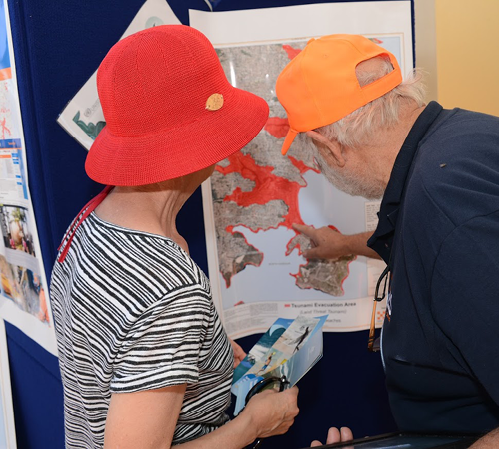 A photo of two senior community members examining a map on a noticeboard.