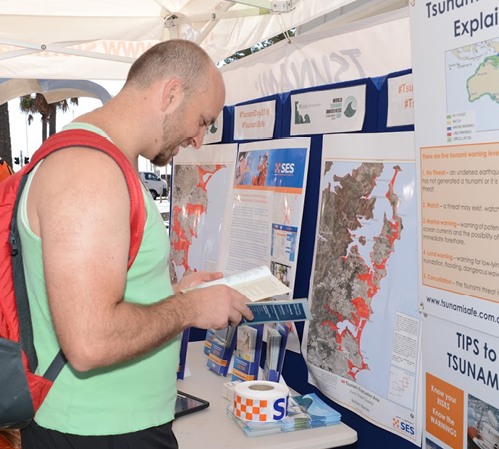 A photo of a young man with a backpack reading a brochure next to a display of SES tsunami information materials.