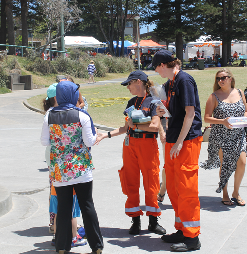 A photo of NSW SES personnel handing out brochures about tsunami risk to people in their local area.