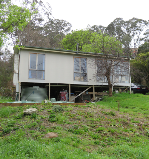 A photo of a typical house with human-made and natural fuel sources in Wye River. It shows a small fibro house on stilts, with grass and trees around it.