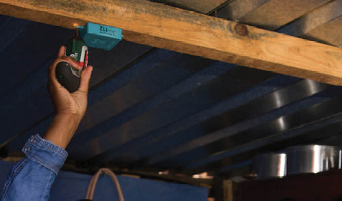 A photo of someone installing a Lumkani by screwing it into a wooden beam.