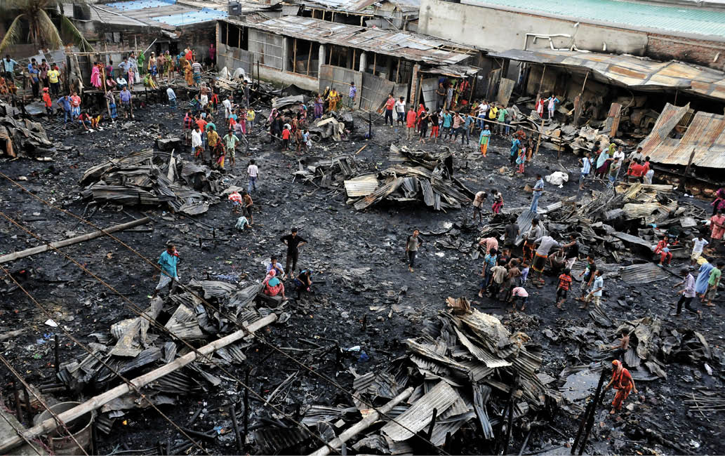 A photo of a slum area ravaged by fire. There are many people on the ground moving around.