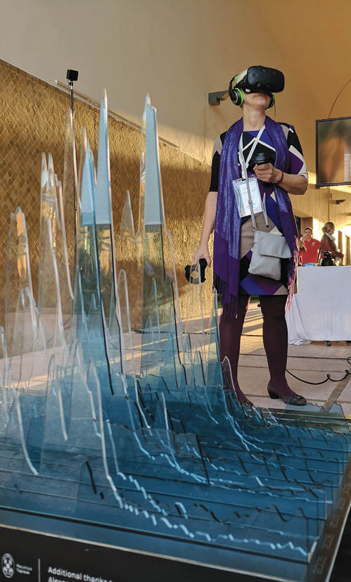 A photo of someone wearing virtual reality goggles, and standing beside a sculpture of a graph showing the changes in Arctic sea ice volume. The lifesize 3D graph looks like icebergs.