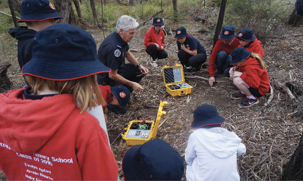 A firefighter is kneeling on the ground in bushland, talking to children. He is showing them some of the equipment that firefighters use.