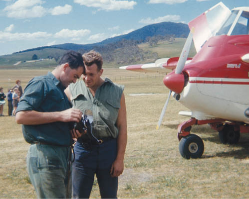 A photo of two men standing in front of the prop plane. One is holding some equipment, and both men are looking at it closely.