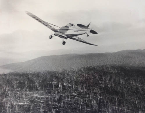 A photo of a plane flying over bushland.