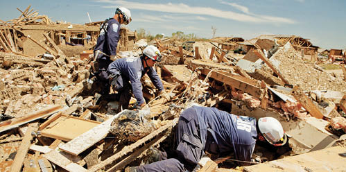 A photo of rescue workers searching through the rubble after homes have collapsed.