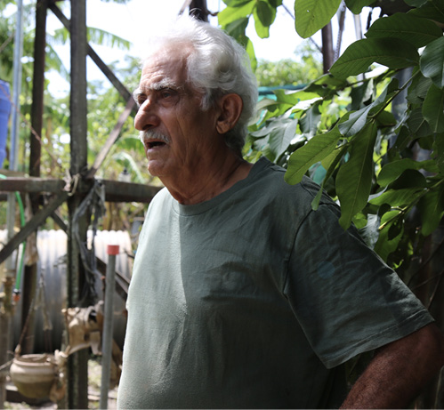 Photo of Emmanuel Vella looking at damage near his home.