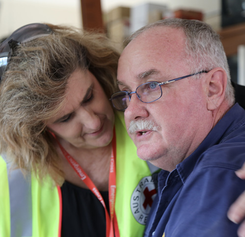 Photo showing Red Cross volunteer Tammy Evans comforting John Nolan with her arm around his shoulders.