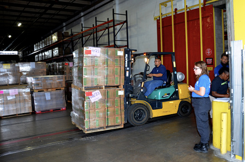 Workers in a warehouse are transporting palettes of supplies with a forklift.