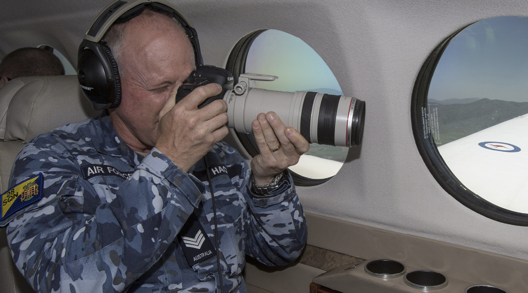 An image of an ADF member taking pictures from the window of an aeroplane.