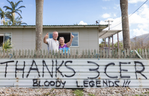 Image of two people standing in front of a home and behind a fence, holding their thumbs up. On the fence are the words 'Thanks 3CER. Bloody legends'.