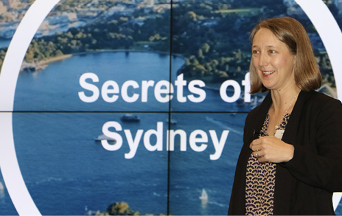 Image of Beck Dawson speaking in front of an aerial photo of Sydney, with the words 'Secrets of Sydney' on it.