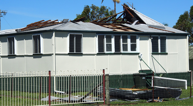 Image of a house with its roof partially torn away.